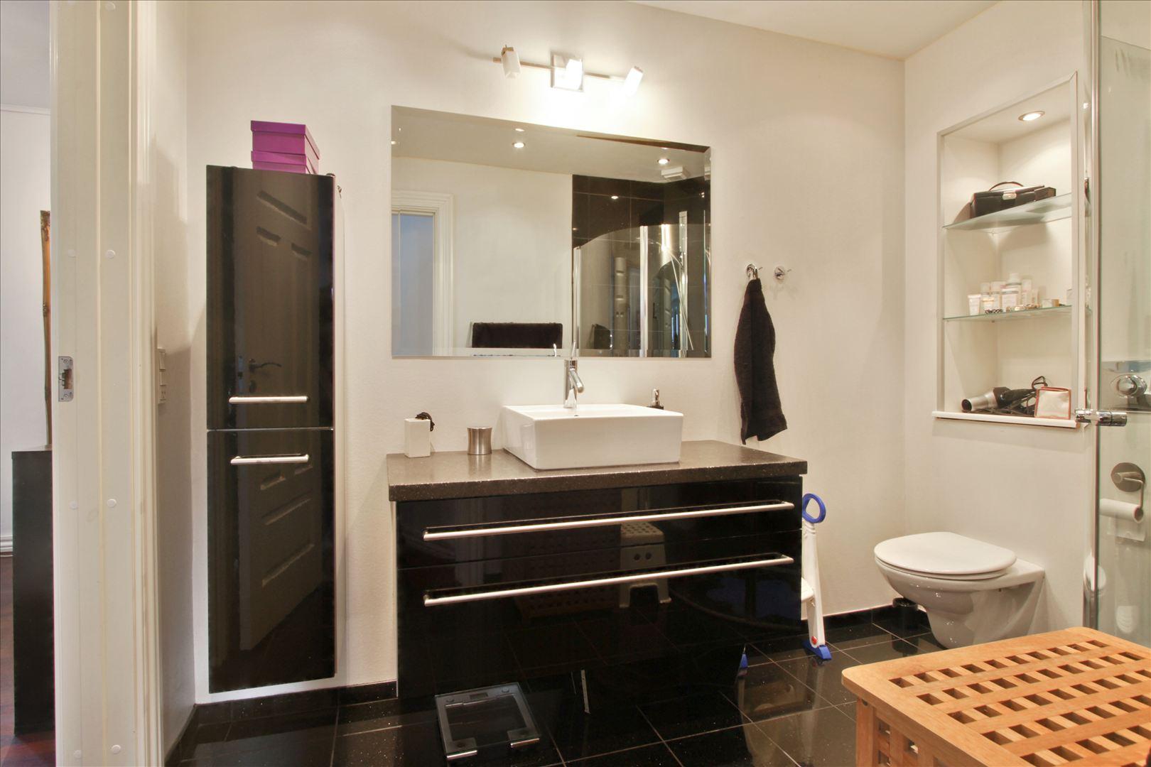 Lækkert badeværelse med black galaxy granit på gulvet og væggen i badet.
