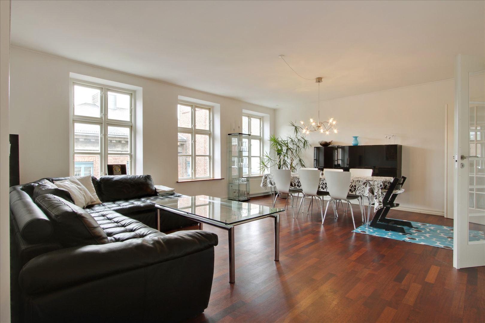 Rummelig stue med franske døre mod køkkenet. Der er ens trægulve i hele lejligheden og der er ingen bundstykker i dørene for, at lave overgangen fra de enkelte rum pænere.